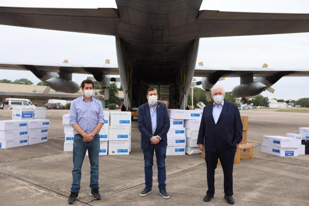 Ginés y ministros delante de cajas con respiradores y de avión Hércules