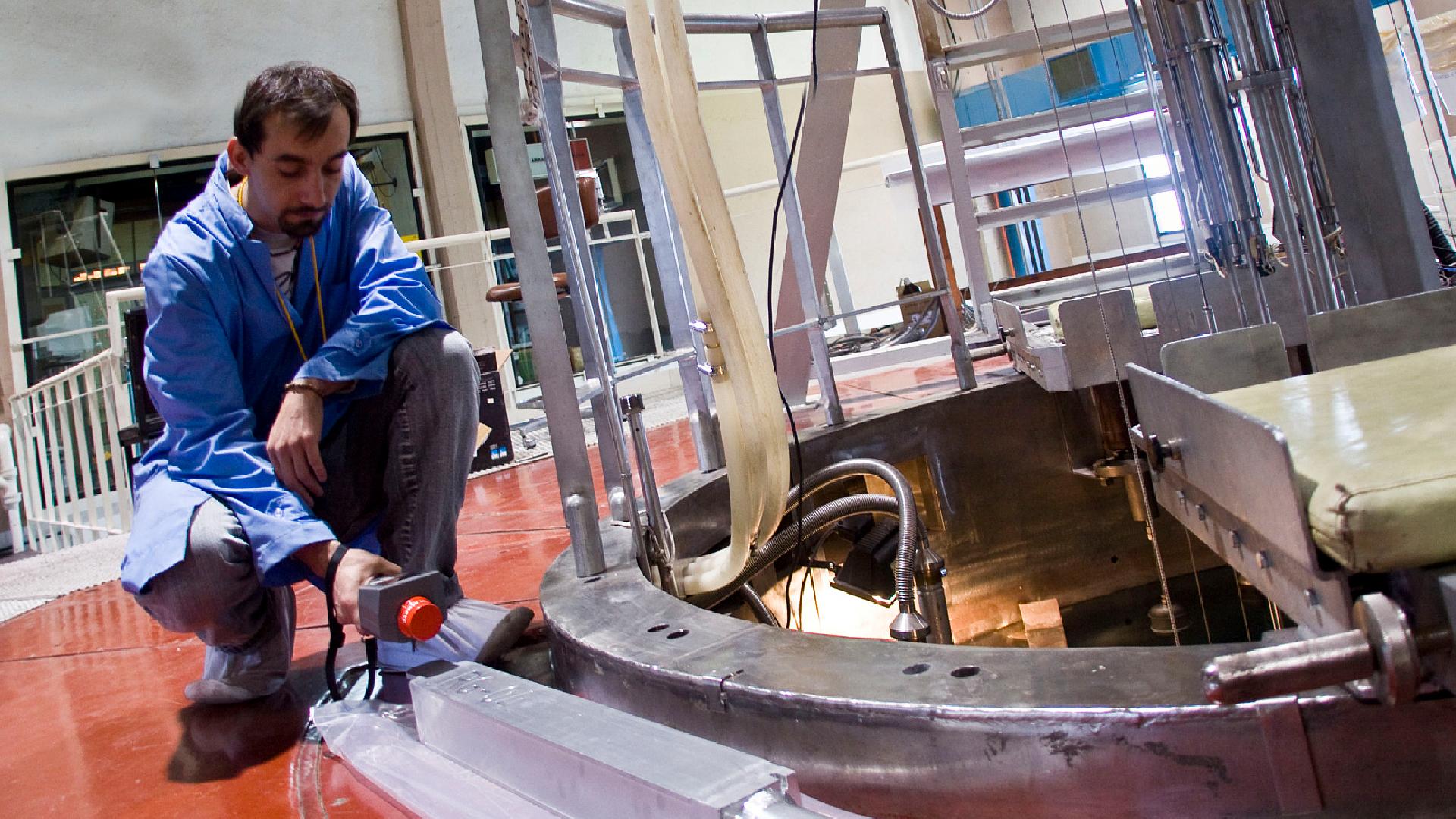 Un científico del Instituto Balseiro realiza mediciones sobre un elemento de prueba en la boca del reactor de investigación RA-6