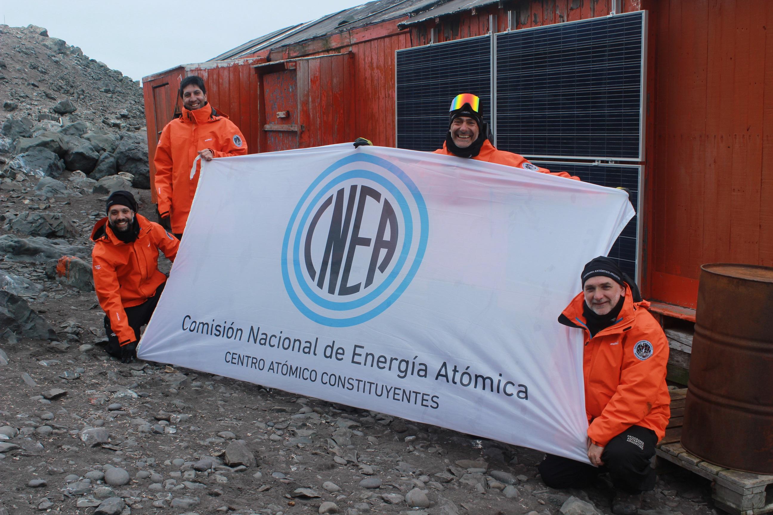 Equipo del Departamento Energía Solar de la CNEA sostiene la bandera en la Antártida