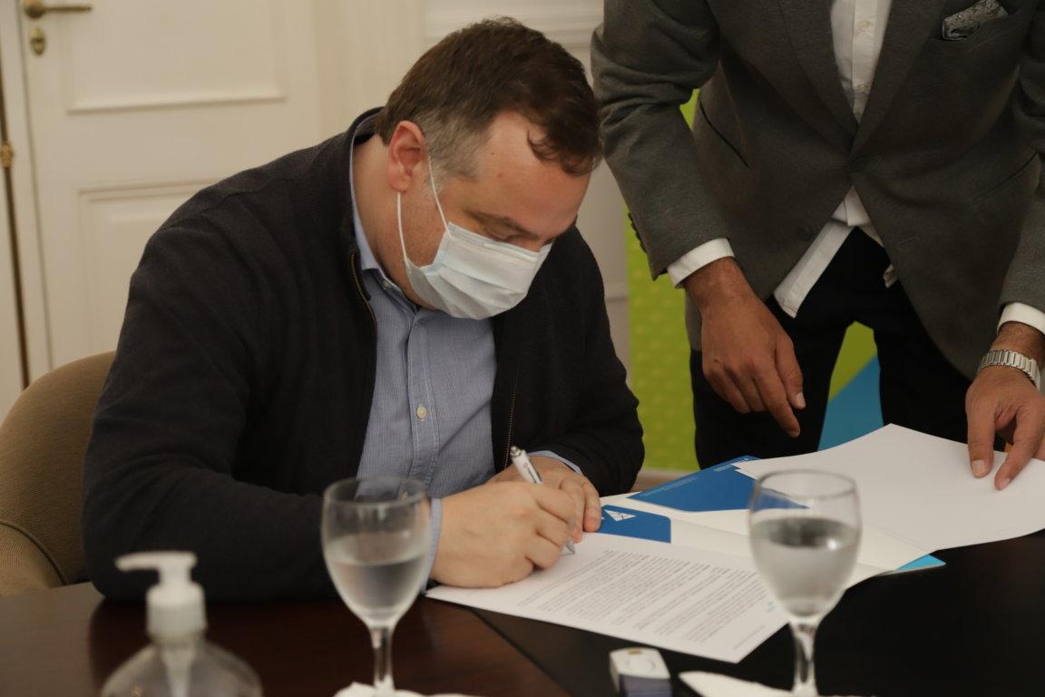 Juan Debandi firmando el convenio